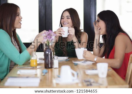 Cute young women having coffee and enjoying themselves at a restaurant - stock photo