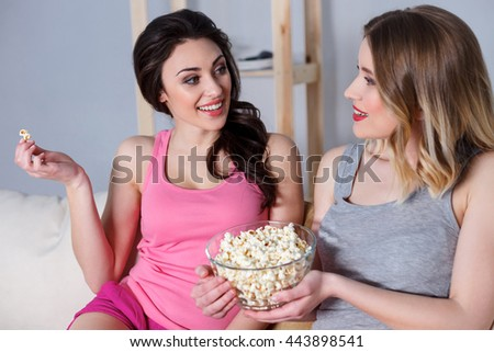 Cute young women watching tv at home - stock photo