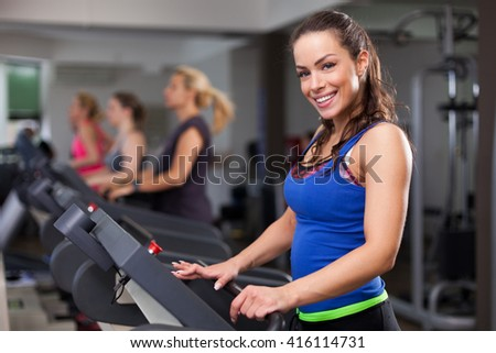Cute young Young woman exercising on a treadmill at a gym  - stock photo