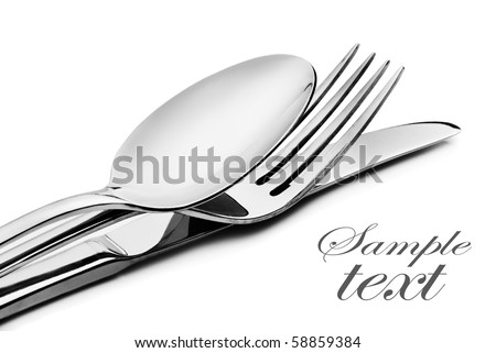 Cutlery - a spoon, fork and knife stacked up on a white background with space for text (focus on the fork) - stock photo