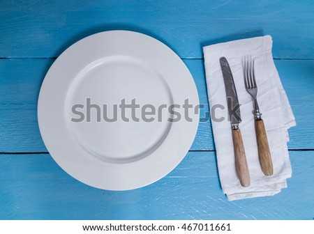 Cutlery and plate on blue wooden background.