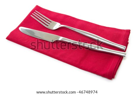 cutlery fork and knife on red serviette - stock photo