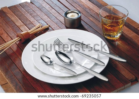 Cutlery on white plate - stock photo