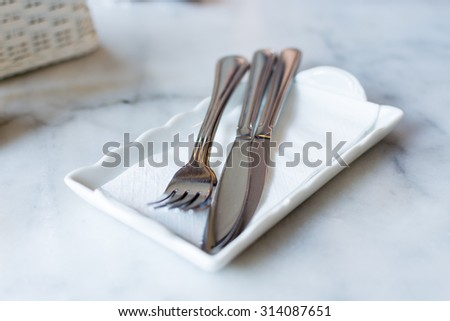 Cutlery set:  fork and knife on white napkin.