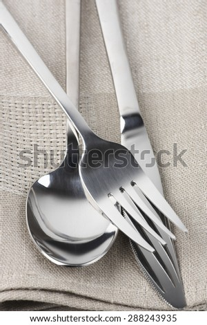 Cutlery set: spoon, fork and knife on linen napkin close-up.  - stock photo