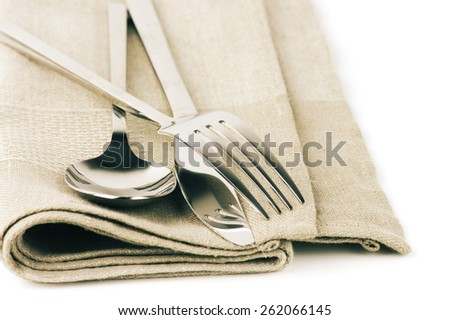 Cutlery set: spoon, fork and knife on linen napkin close-up. Toned image. - stock photo