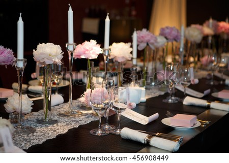 Cutlery table covered in natural crocodile skin. Glasses and plates, forks and knives, napkins and buttons for a luxurious celebration in anticipation of guests. Luxury festive table.