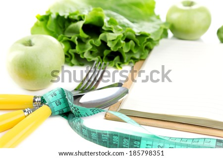Cutlery tied with measuring tape and book with greens close up