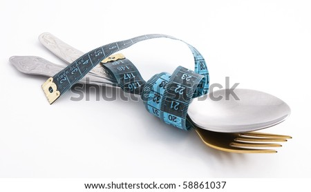 Cutlery with a measuring tape, diet, moderate eating - stock photo