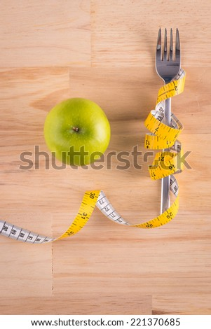 Cutlery with tape. Symbol for diet and weight loss. Green Apple, Knife and fork wrapped in tape measure on wooden table with copy space - stock photo