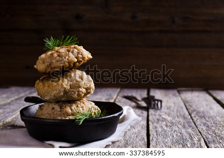 Cutlets from minced meat and rice in a metal pan. Selective focus. - stock photo