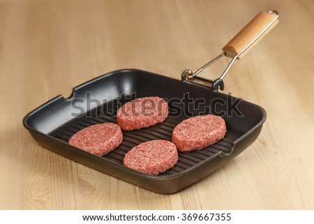 Cutlets in a pan on a wooden table - stock photo