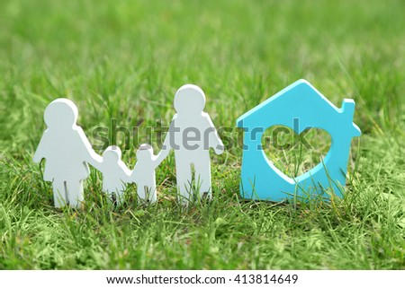 Cutout figurine of a family and house on green grass background - stock photo