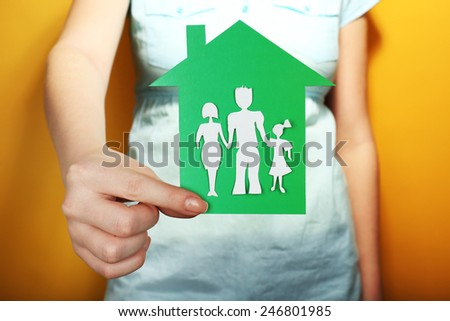 Cutout house with paper family in female hand on colorful background - stock photo