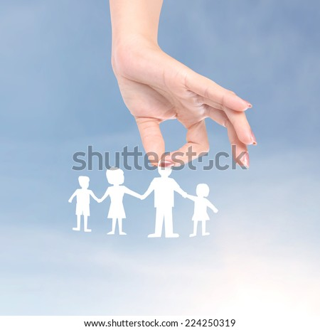 Cutout paper chain family with the protection of cupped hands  - stock photo