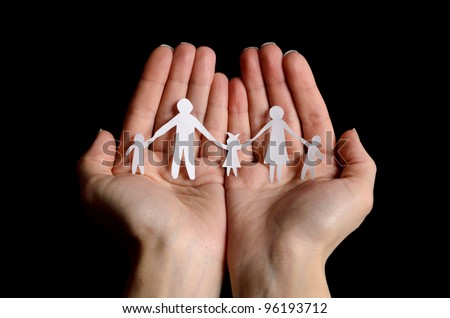 Cutout paper chain family with the protection of cupped hands, concept for security and care on black background - stock photo