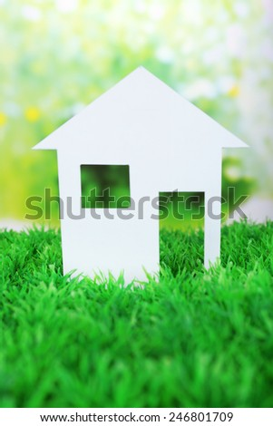 Cutout paper house on green grass and bright blurred background - stock photo