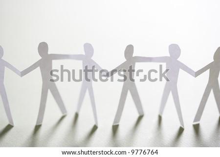 Cutout paper men standing holding hands. - stock photo