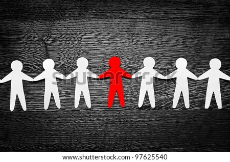 Cutout paper people on wooden table and artistic shadows added - stock photo