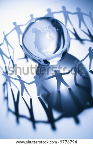 Cutout paper people standing around globe holding hands. - stock photo
