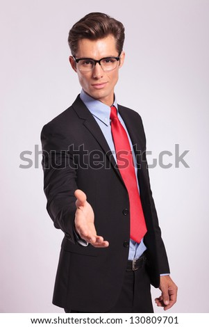 cutout picture of a young business man offering to shake hands, on a gray background - stock photo
