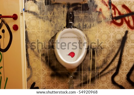 cutout view of a public restroom, whose walls, urinals and the door are sprayed with graffiti - stock photo