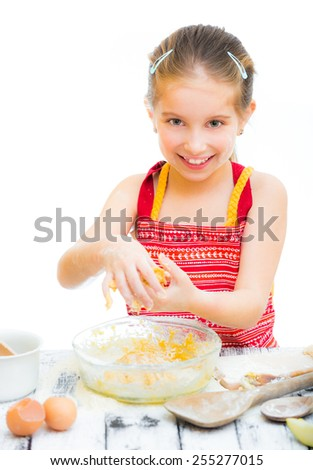 cutre little girl making dough, on a white background - stock photo