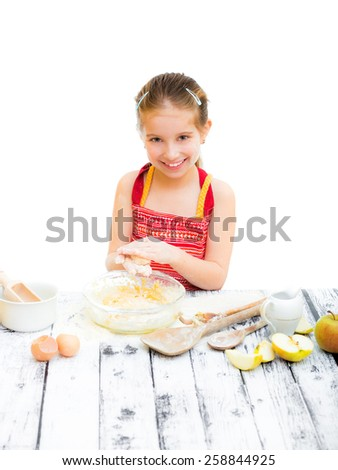 cutre little girl making dough on the kitchen - stock photo