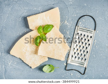Cuts of Parmesan cheese with metal grater and fresh basil over concrete textured background, top view - stock photo