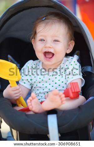 cutte little baby have fun and play with toys in carriage on summer vacation on beach