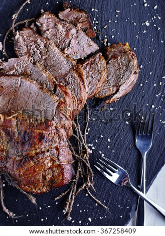 Cutted roasted beef on black stone with two forks near it. - stock photo