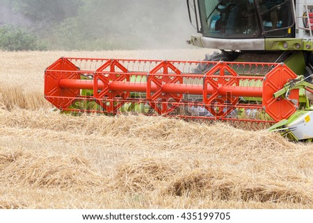 Cutterbars on a combine harvester harvesting a crop of wheat , Triticum aestivum, for fodder in an agricultural field , close up detail - stock photo