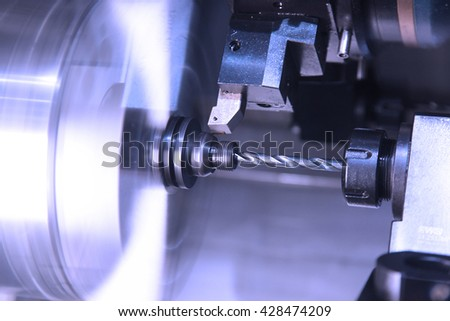 cutting and drilling of metal parts processing on lathe in workshop. Selective focus on tool - stock photo