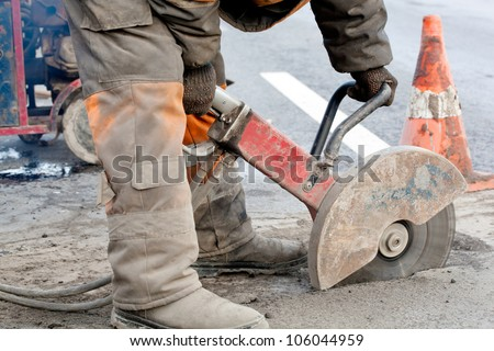 Cutting asphalt road for repair by hydraulic driven angle grinder; road works; upgrading road surfaces; horizontal orientation - stock photo