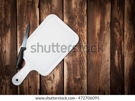 Cutting board and kitchen knife on wood background