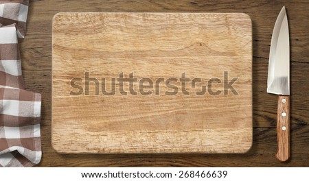 Cutting board and knife on old wood table with picnic tablecloth background - stock photo