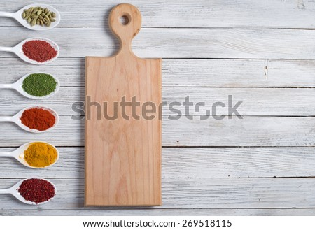 cutting board and spices on a wooden table - stock photo