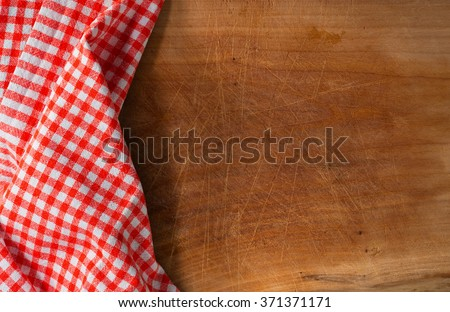 Cutting Board Covered with Tablecloth / Used wooden cutting board partially covered with a red and white checkered tablecloth. - stock photo