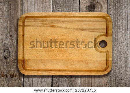 Cutting board on old wooden background - stock photo