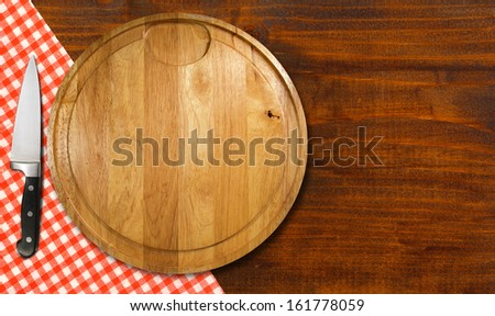 Cutting Board on Wood Table / Round cutting board with red checked tablecloth and kitchen knife on brown wooden table - stock photo