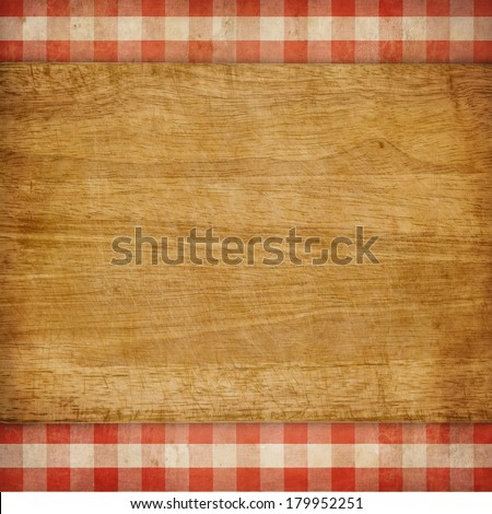 Cutting board over red grunge checked gingham picnic tablecloth background - stock photo
