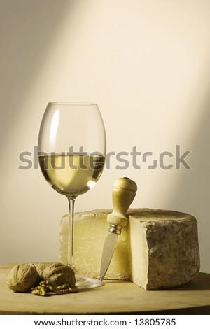 Cutting board with genuine Italian food. White wine glass and ripe hard cheese. - stock photo