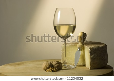 Cutting board with genuine Italian food. White wine glass, ripe hard cheese from ewe's milk and walnuts. Warm ray of light in the background. Space for text - stock photo
