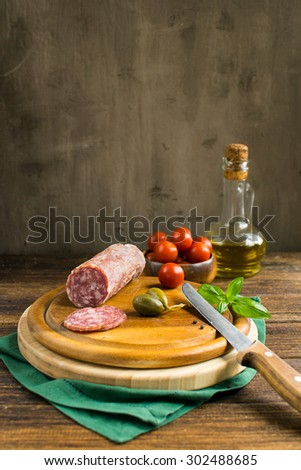 cutting board with Italian tapas on a wooden table