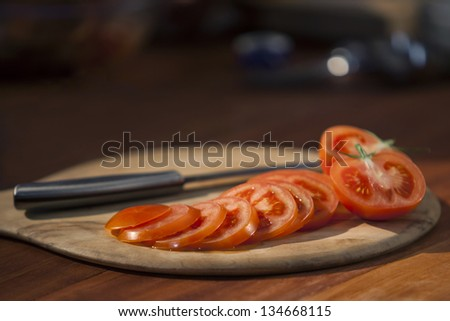 Cutting board with knife and red thinly sliced tomatoes on top. Tomatoes in foreground are in focus but image has a shallow depth of field.  Image has slight bit of noise. Captured at 640 ISO. - stock photo
