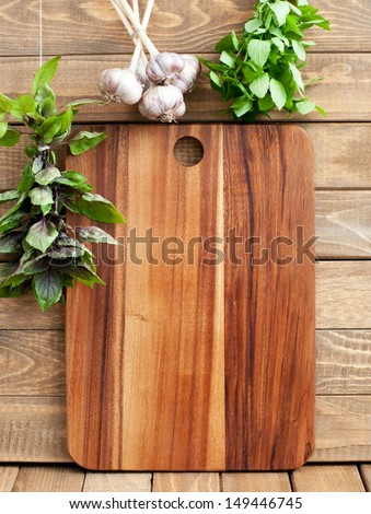 Cutting board with space for text, fresh basil and garlic on wooden background, vertical - stock photo