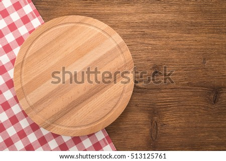 Cutting board with tablecloth on wooden background