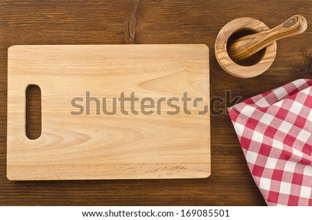 Cutting board with towel and bowl on wooden background  - stock photo