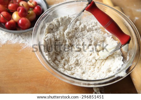 Cutting butter into flour to make pastry crust for cherry pie, copy space included - stock photo