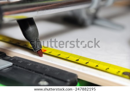 Cutting ceramic tiles with manual tile cutter - stock photo